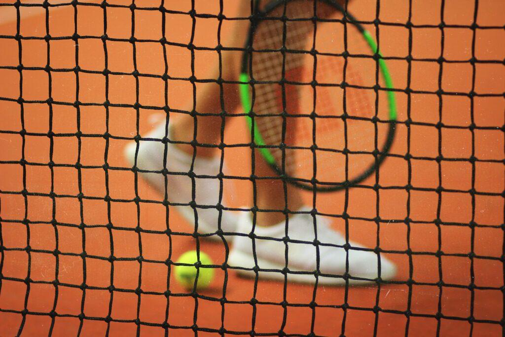 Tennis shoes behind a net