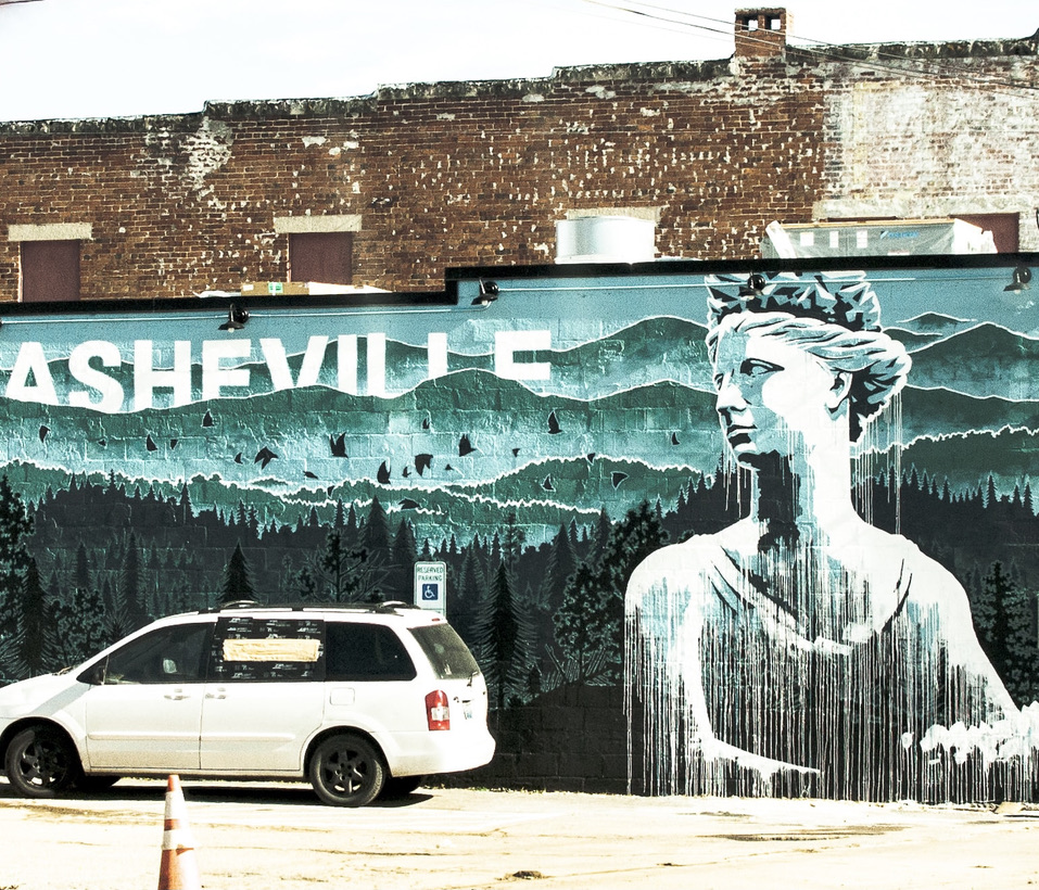 A mural of a woman with a white car in front
